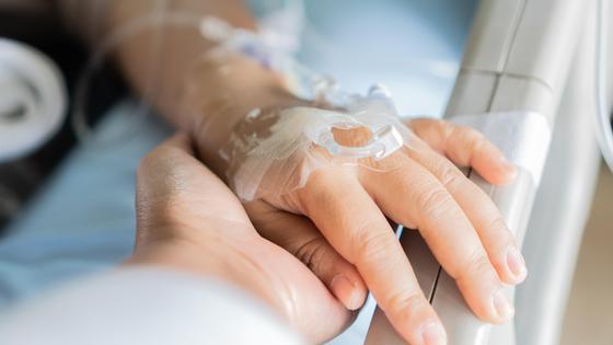 Рука держит руку с катетерами на больничной койке