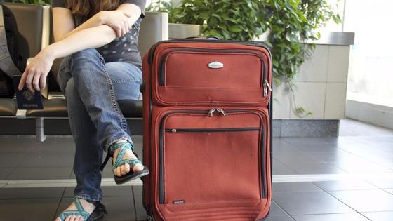 Девушка с красным чемоданом сидит в аэропорту