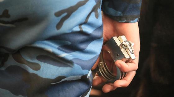 Полицейский держит наручники
