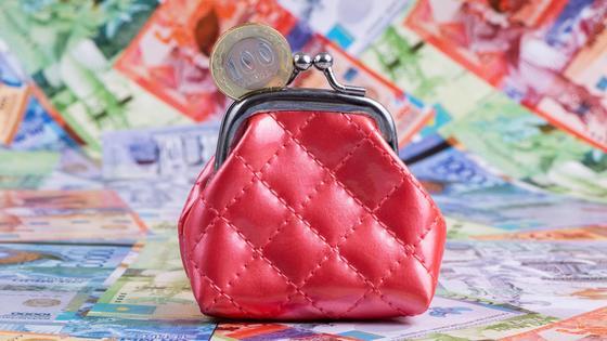 Красный кошелек стоит среди купюр тенге