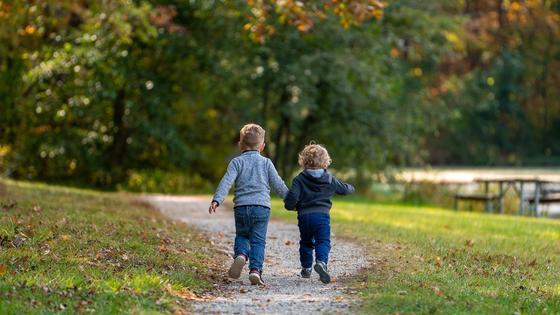 двое детей бегут по тропинке в парке