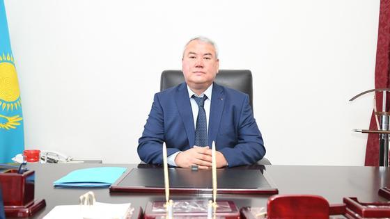 Серикжан Ерекешев сидит за столом на рабочем кресле