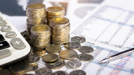 Монеты, калькулятор и ручка лежат на финансовом отчете