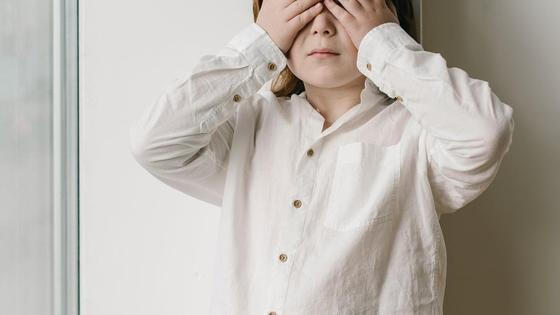 Мальчик закрывает лицо руками