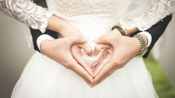 Жених и невеста делают из рук сердечко