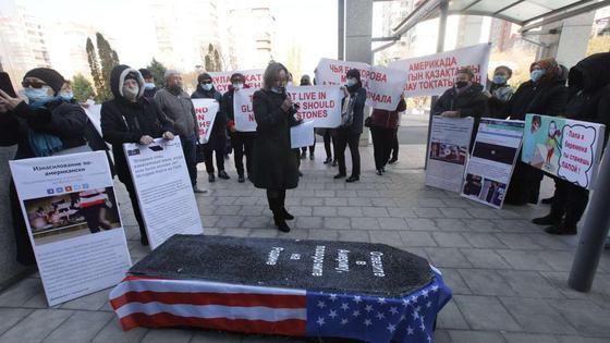 Люди с плакатами собрались вокруг гроба