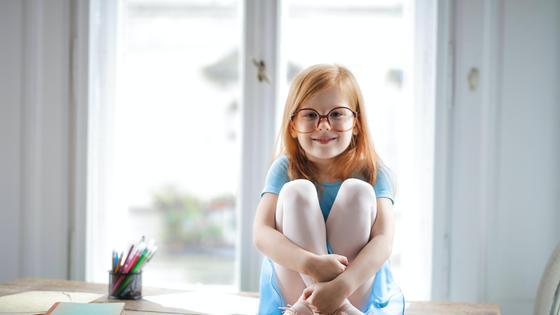 Маленькая девочка сидит в очках