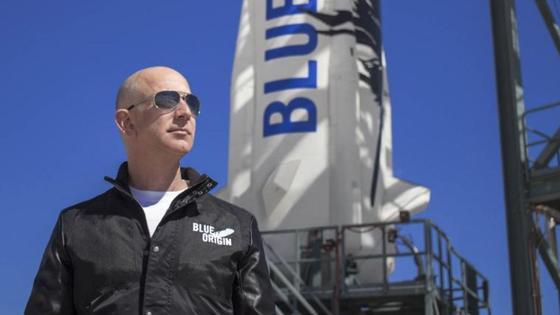 Джефф Безос стоит на фоне ракеты