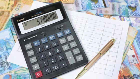 Калькулятор лежит на купюрах