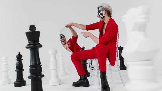 Молодой человек в красном костюме смотрит в зеркало рядом с шахматными фигурами