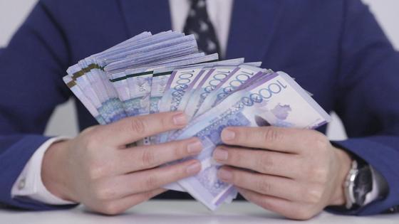 Мужчина держит в руках крупную сумму денег