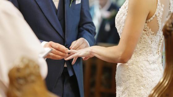 Жених надевает кольцо на палец невесты
