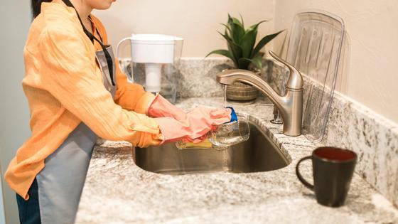 Женщина моет посуду в раковине