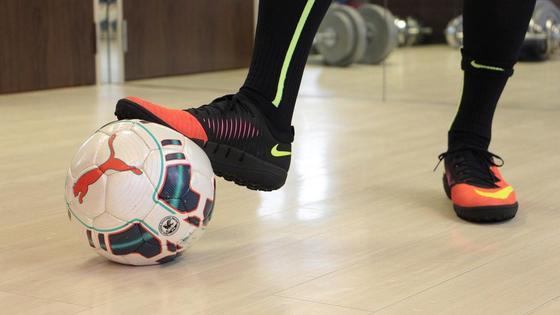 Футболист ногой придерживает мяч