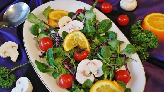 Праздничный салат с овощами и зеленью на красивом блюде