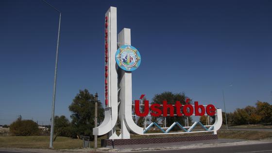 Указатель город Уштобе стоит на дороге