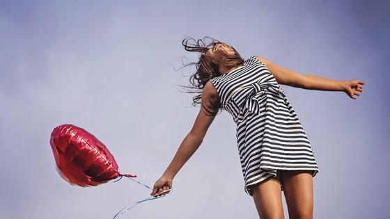 Девушка смеется в платье с шариком
