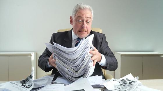 Мужчина разбирает кипу бумаг