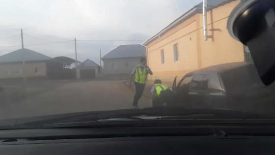Двое полицейских задерживают водителя автомашины