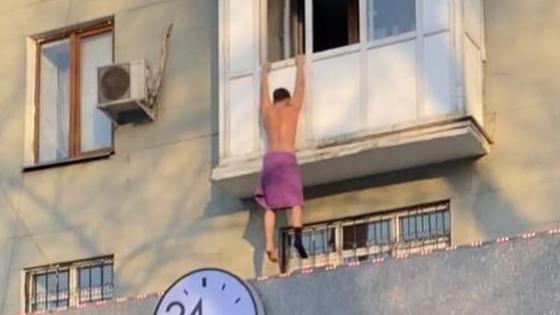 Мужчина висит на балконе в розовом полотенце и одном носке