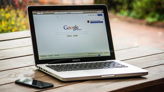 Ноутбук стоит на столе рядом с телефоном