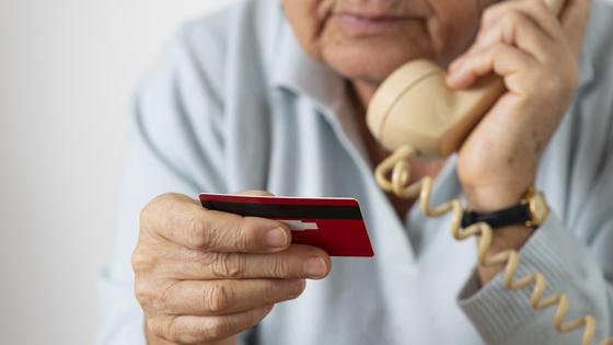 Пенсионерка держит телефон и банковскую карту