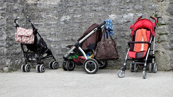Детские коляски стоят у стены