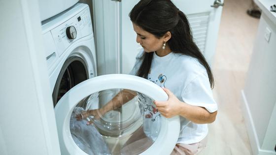 Девушка кладет вещи в стиральную машинку