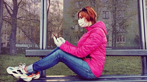 Девушка сидит с телефоном на лавочке