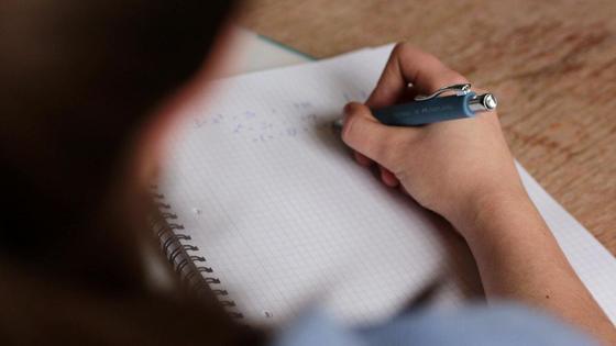 Девушка пишет ручкой в тетради