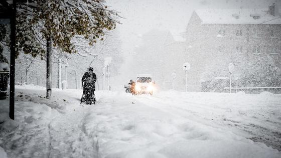 Человек идет по улице во время снегопада на фоне деревьев, зданий и автомобиля