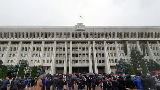 Толпа людей стоит у здания Жогорку Кенеша