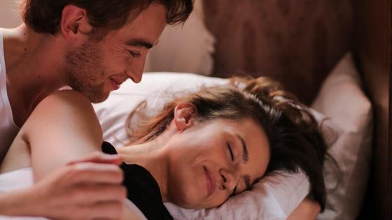 Мужчина и женщина улыбаются, лежа в постели