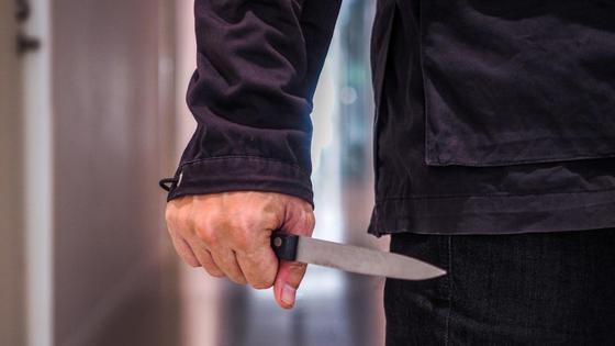 Мужчина стоит с ножом в руке