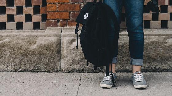 Девушка держит рюкзак