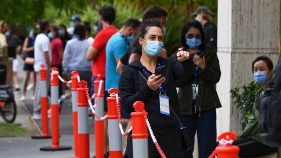 Девушка в маске стоит в очереди