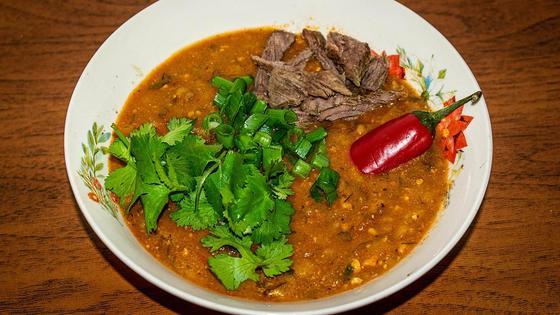 Суп харчо в тарелке с зеленью и острым перцем