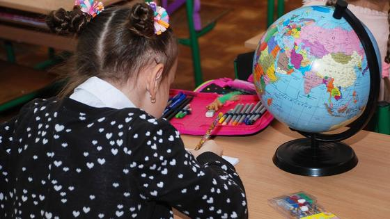 Девочка сидит за партой и учит уроки