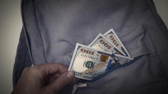 Рука вытаскивает банкноты из серого рюкзака