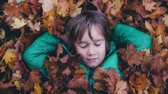 мальчик лежит в осенней листве