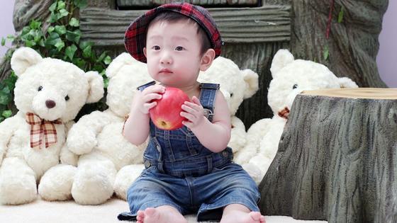 Корейский мальчик с яблоком и игрушками