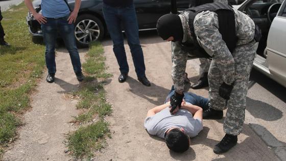 боец спецназа проверяет лежащего на земле задержанного