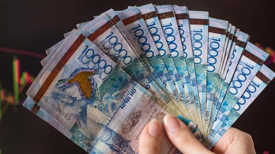 Трейдер держит в руках пачку денег