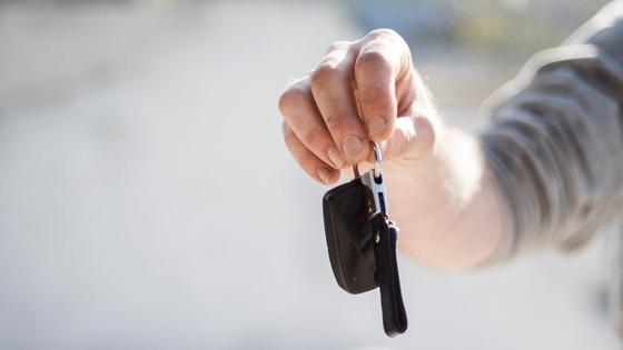 Мужчина держит в руке ключи от машины