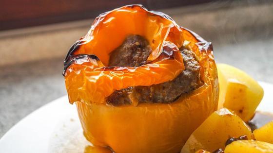 Желтый фаршированный перец с картофелем на тарелке