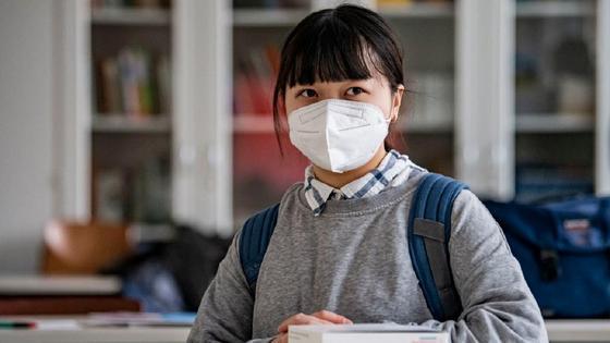 Ученица в маске сидит за партой