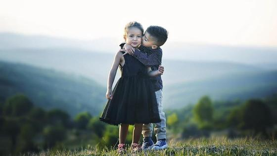 мальчик целует девочку в щечку