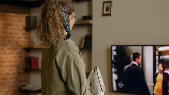Девушка гладит и смотрит телевизор