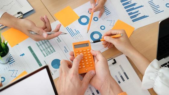 Руки с ручкой, карандашом и калькулятором над листами с графиками
