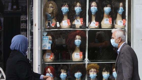 Мужчина проходит мимо витрины с масками